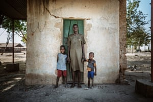 A woman stands with her two children outside a square building in Bentiu Town, South Sudan. Formerly attached to a larger building, the square room, which is all that remains now, is where this young family has been living for the past six months.