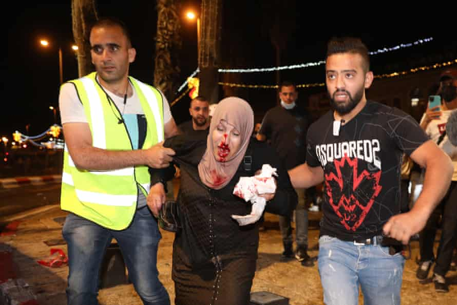 People help an injured Palestinian woman during a demonstration at Damascus Gate to support Palestinian families facing eviction from their homes in the Sheikh Jarrah neighborhood of Jerusalem.