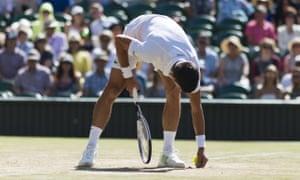 Novak Djokovic inspects the grass court at Wimbledon on Saturday.