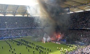 Police officers and security staff stand on the pitch when supporters light fireworks as Hamburg's proud Bundesliga record came to an end