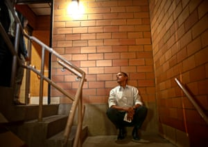 Barack Obama listens from a back stairwell as he is introduced during his first election campaign