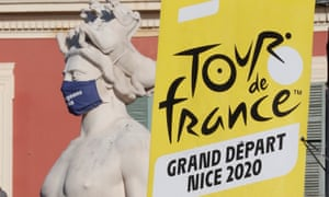 A Tour de France banner next to a statue with a protective face mask in Nice