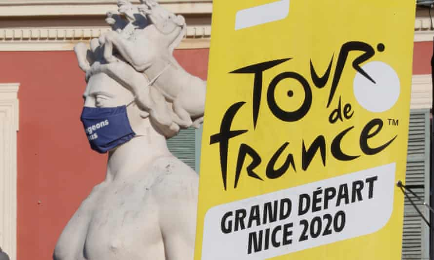 A Tour de France banner next to a statue with a protective face mask in Nice.
