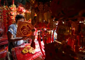 Bangkok, Thailand. Chinese-Thai woman looks at decorations as preparations are underway for celebrations of the Lunar New Year in the city's Chinatown