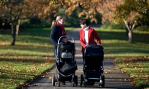 Two mothers pushing buggies in the park.