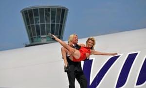 Sir Richard Branson holds up Kate Moss