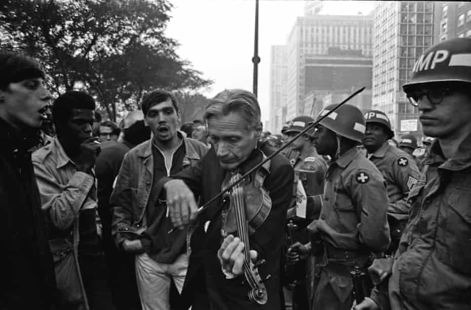 At the Democratic National Convention in Chicago, at about 6 a.m. a delegate played violin standing between troops and demonstrators across the street from the Conrad Hilton hotel, the headquaters of the Democratic National Committee.