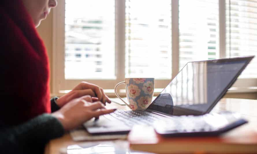A woman types at a laptop