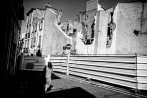 A woman walks past the steel sheets sealing off the Ilot Puig. The attempted destruction of this set of houses on a corner of the Place du Puig – a popular meeting point for the community – sparked protests against large-scale demolitions in St Jacques.