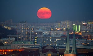 A blood-red moon rises above the city
