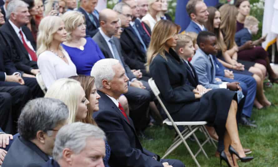 Karen and Mike Pence sit across the aisle from Melania Trump and Barrett's family as Barrett speaks.