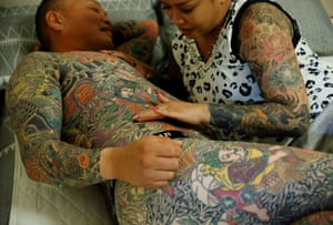 Mina Yoshimura inspects a new tattoo on her husband, Hiroshi Yoshimura. 'Well, if I had tattoos and he didn't, he'd be able to go places that I couldn't. But since we're both the same, we can go anywhere together. I think that's nice.'