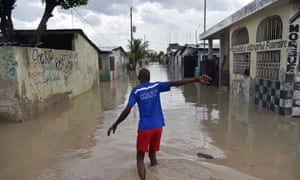 A man walks down a flooded street in the Cite Soleil area of Port-au-Prince