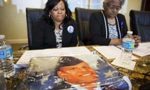 A blanket decorated with the portrait of Anthony Hill rests on a table as Hill's mother Carolyn Baylor Giummo, left, and grandmother Theola Baylor, talk to media.