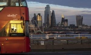 A London bus crosses Waterloo bridge against a backdrop of skyscrapers, including 22 Bishopsgate office tower, in City of London