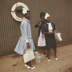 Three women wait with their hand luggage at Southampton in 1962