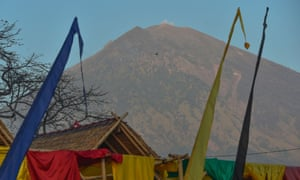 Mount Agung seen past huts at Amed beach: a diving instructor there said tourists had packed up and left.
