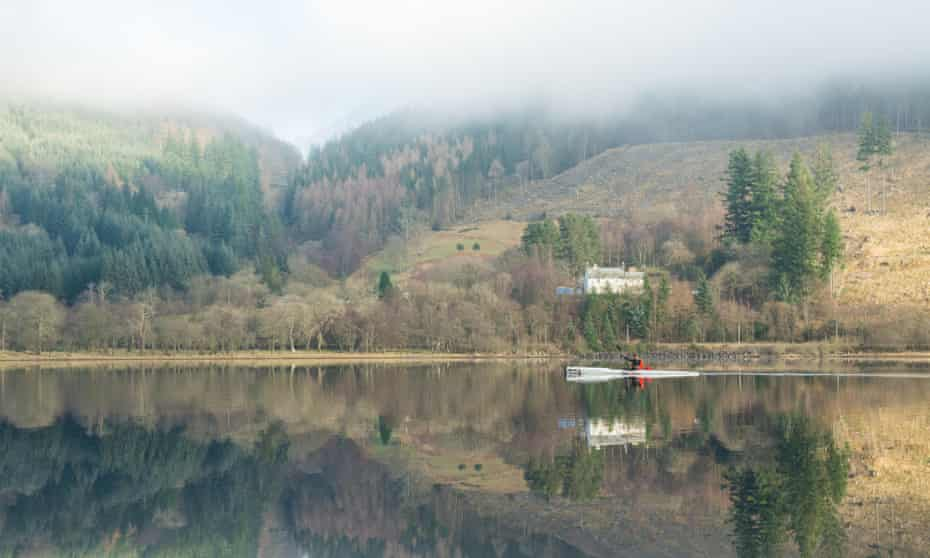 a kayaker reflected in the still water of Loch Lubnaig