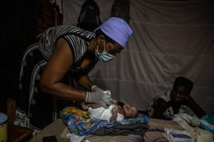 Midwife Ivy Gatsi puts a cloth nappy on a newborn baby girl who was delivered early hours of the morning in the delivery room located at her home on 15 January 15, 2021 in Harare, Zimbabwe. Zimbabwe's healthcare system is overwhelmed with the coronavirus pandemic after a severe economic crisis tipped the country into hyperinflation and poverty.