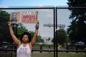 A woman in Washington on Friday holds a placard demanding justice for George Floyd.
