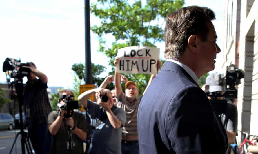 Manafort arrives at court with a protester holding a 'Lock him up' sign.