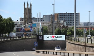 """A giant TV screen displays the 'We Love Manchester"""" logo"""