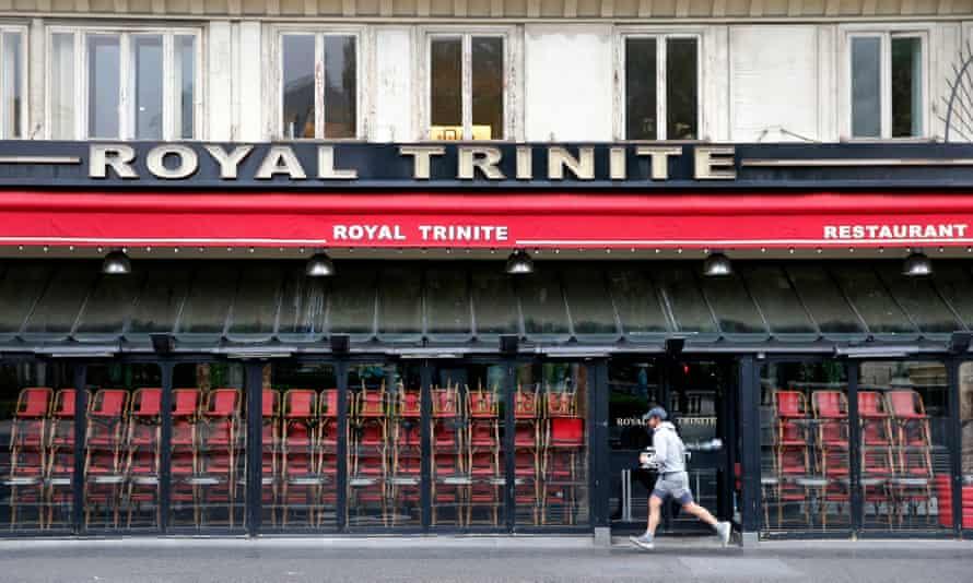 A jogger runs past a closed restaurant in Paris
