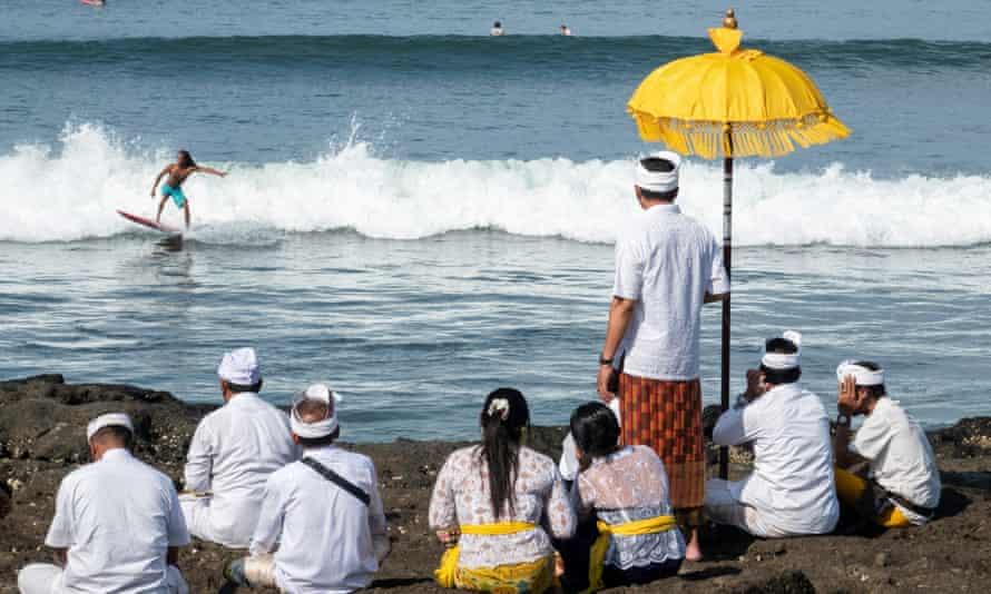Hindus watch a surfer at the beach in Canggu