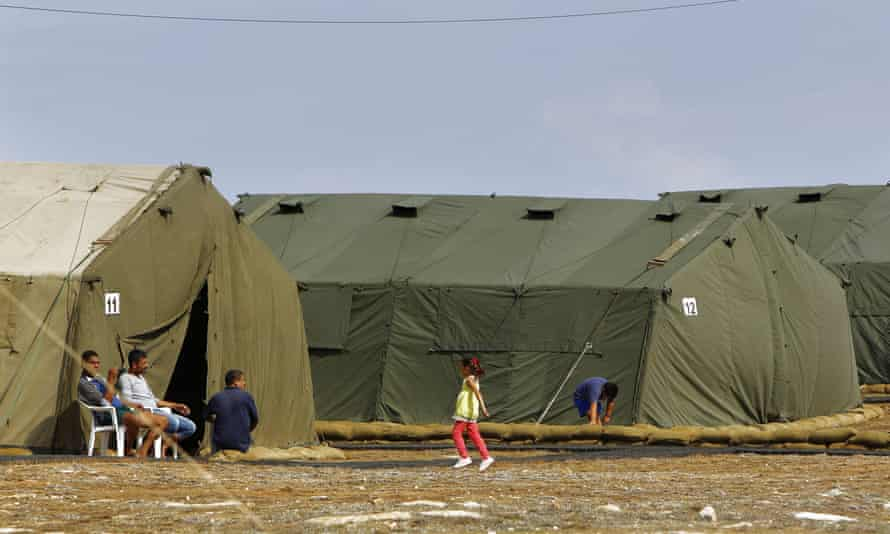 A child plays outside of a tent at the temporary facility at Dhekelia