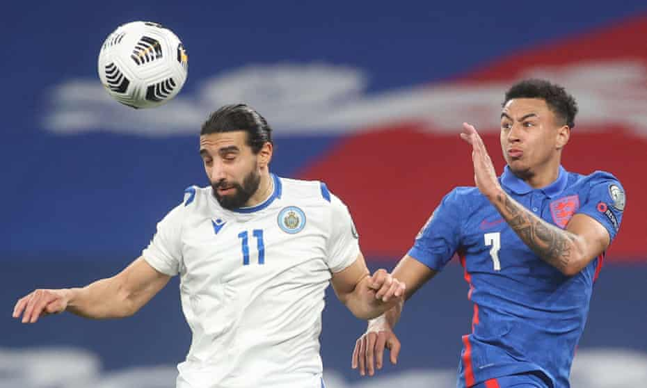 The San Marino defender Manuel Battistini heads the ball under pressure from the England midfielder Jesse Lingard.