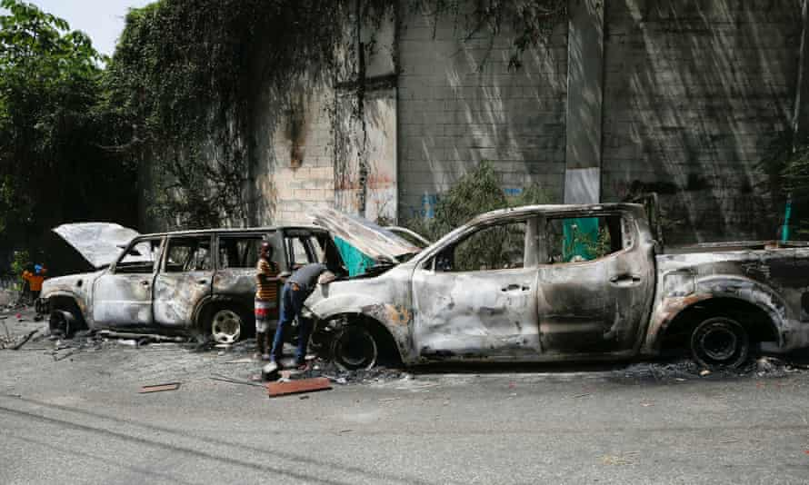Children look for metal pieces in cars burnt by locals after a firefight between police and the suspected assassins of president Moïse