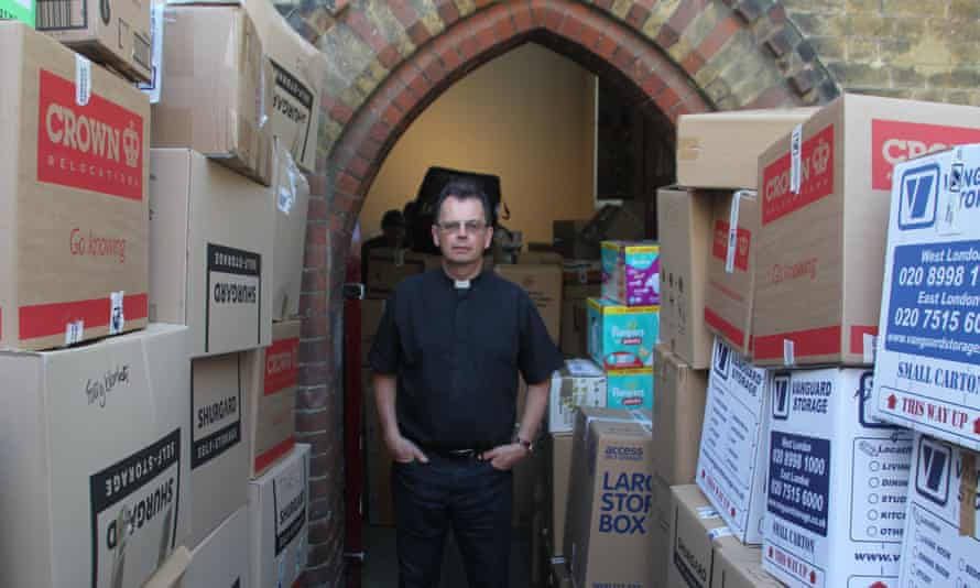 Rev Alan Everett surrounded by donations from the public at the church of St Clement's, Notting Dale, next to Grenfell Tower