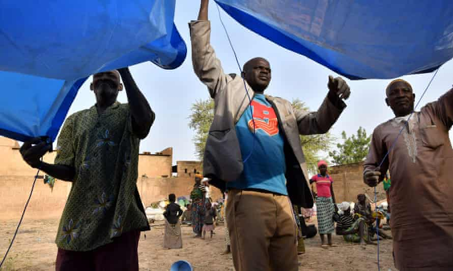 Displaced men who fled from attacks in the town of Roffenega install a tent in Pissila, Burkina Faso.