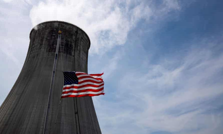 The US flag flies at half mast in front of a coal-fired power plant's cooling tower.
