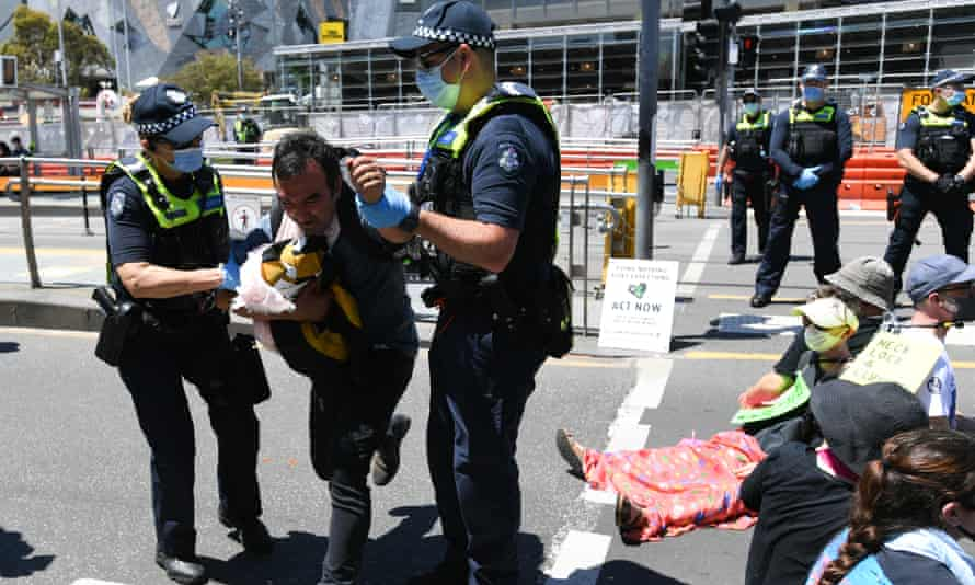 Police remove a protester from the road during a climate protest in Melbourne on Saturday