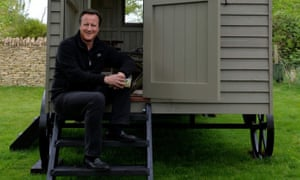 David Cameron relaxes on the steps of his £25,000 luxury garden hut.