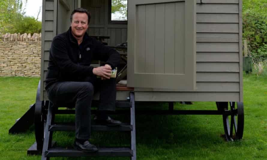 David Cameron relaxes on the steps of his luxury garden hut.