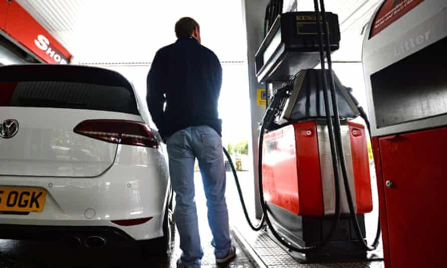 A man fills his car with fuel at a garage