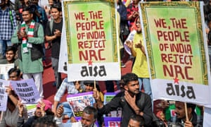 "Group of people, some holding a colourful sign saying ""We the people of India reject NRC"""