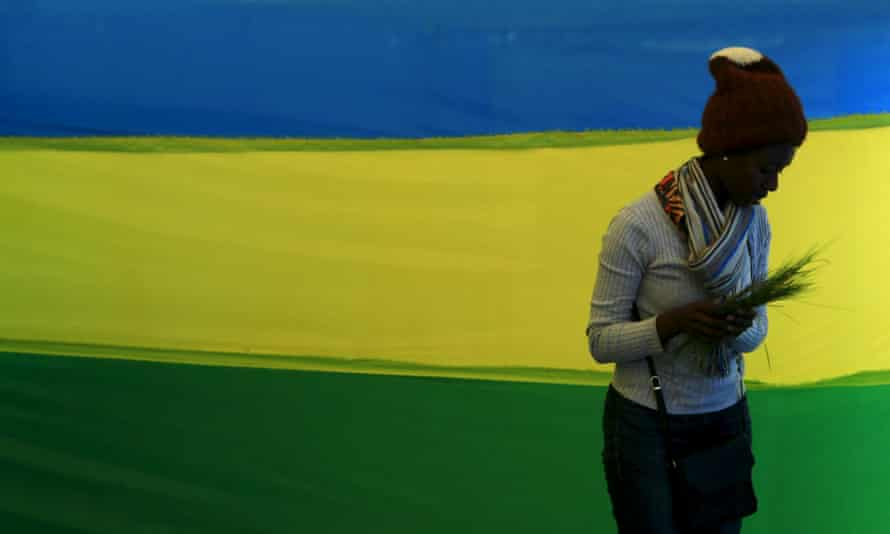 A woman walks past a Rwandan flag at a polling station. The county revised its penal code in 2018, restricting abortion to a narrow set of circumstances.