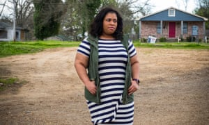 Angie Thomas standing on land in front of her house