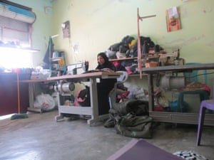 A woman works in a tailor's studio in the village to support her family. She has made hundreds of clothes