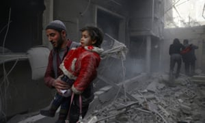 A man carries a child through rubble after a regime airstrike in Douma, Syria