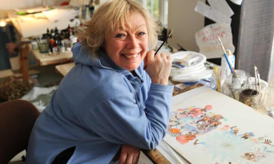 Babette Cole smiling at desk with illustration