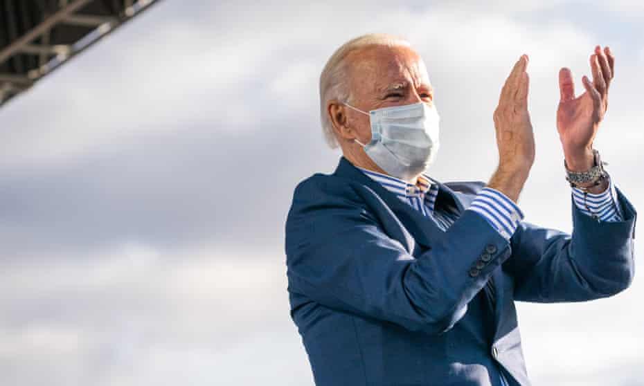 Joe Biden, wearing a mask, claps on stage