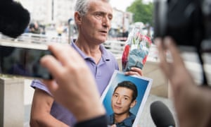 The father of a victim with a photo of his son near the Olympia shopping centre