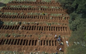 Cemetery workers in protective clothing bury a person at the Vila Formosa cemetery in Sao Paulo, Brazil, on Wednesday
