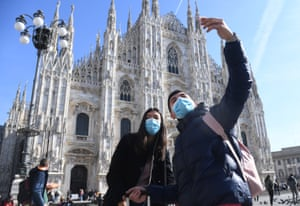 tourists in milan wear face masks as they take a selfie in front of the cathedral