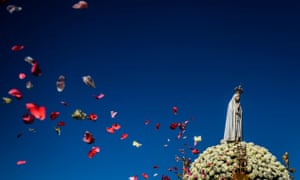 People throw rose petals at the statue of Our Lady Fátima during a procession to the Catholic shrine in Fátima, Portugal