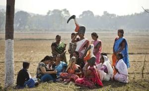 """Wildlife biologist Purnima Devi Barman, second left, who works with a local conservation group called Aranyak, shows photographs of storks to a group of women from the """"hargila army,"""" during an awareness meeting to save the bird, in Dadara village"""
